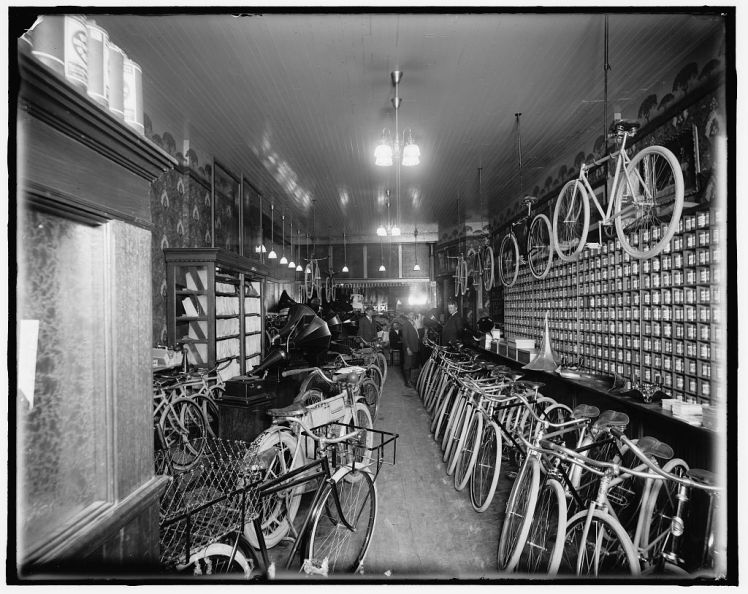 Interior of bike shop, possibly Huber & Metzger Bike Shop on Grand River between Woodward & Griswold.  Photo c. 1900-1920, Detroit Publishing Company.